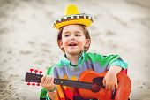 Toned photo of Little happy smiling boy plays his guitar or ukulele