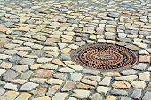 Manhole cover and cobblestones