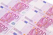 Euro notes aligned as background.