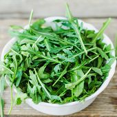 Fresh Arugula In White Bowl On Wooden Table