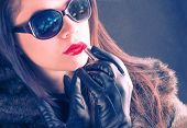 Glamorous young woman paint her lips, city lights reflection on sunglasses