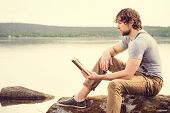 stock photo of scandinavian  - Young Man reading book outdoor with scandinavian lake and mountains on background Education and Lifestyle Travel concept - JPG