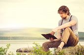 image of scandinavian  - Young Man reading book outdoor with scandinavian lake and mountains on background Education and Lifestyle Travel concept - JPG