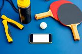 image of ping pong  - Smartphone with white screen on a blue table with ping pong rackets - JPG