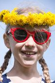 pic of cheater  - young smiling caucasian girl portrait in yellow dandelions garland on the head with two pigtail braids and red sunglasses - JPG