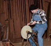 stock photo of blacksmith shop  - blacksmith sharpens an axe on a retro stone wheel in a tool shop - JPG