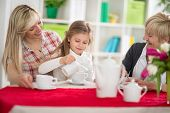 stock photo of grandma  - Cute girl serving tea her mom and grandma - JPG