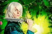 stock photo of fantasy  - Beautiful blond elf with a dagger in his hand in the magic forest - JPG