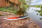 stock photo of horsetooth reservoir  - red stand up paddleboard  with a paddle on rocky lake shore  - JPG
