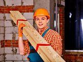 picture of millwright  - Happy man in builder helmet carry boards indoor - JPG