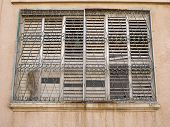 picture of lockups  - Grungy window with rusty iron bars in an urban downtown area - JPG