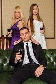 stock photo of threesome  - A guy and two girls in the room - JPG