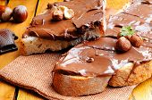 picture of hazelnut  - Two slices of bread with chocolate cream and hazelnuts on a wooden table - JPG