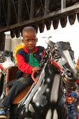 picture of carnival ride  - RUSTENBURG SOUTH AFRICA - MAY 25: Black African Boy riding on electronic horse ride at Rustenburg Fair on May 25 2014 in Rustenburg South Africa.