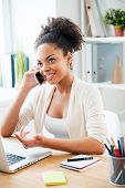 image of people talking phone  - Beautiful young African woman talking on the mobile phone and smiling while sitting at her working place in office - JPG