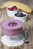 stock photo of banana  - Smoothies of frozen strawberries blueberries and banana with yogurt. Blueberries and strawberries in a white cups and a banana in the background on a wooden table.