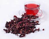stock photo of hibiscus  - Cup of hibiscus tea and a heap of dried petals of hibiscus - JPG