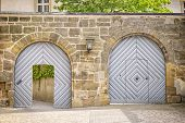 stock photo of gate  - Image with two gates in a wall where a gate is open the other is closed - JPG