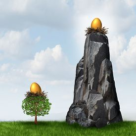 stock photo of retirement  - Secure investment choice as a golden nest egg in a low tree and another retirement or savings gold fund on a high hard access rock mountain as a financial and business metaphor for retirement security safeguard - JPG