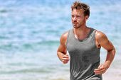 Active runner sweating running on beach. Handsome young male athlete wearing grey tank top for sweat poster