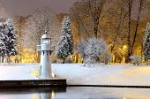 Snow-covered trees a lighthouse reflecting in Riga canal in winter by night.