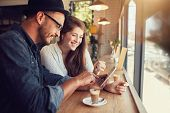 Happy Couple In A Coffee Shop Using Digital Tablet poster