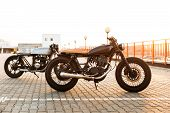 Постер, плакат: Two Black And Silver Vintage Custom Motorcycles Caferacers