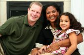 picture of middle class  - Interracial family sitting together at home - JPG