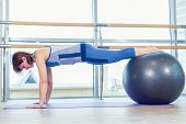 Young and athletic girl using fitness ball in a gym. poster