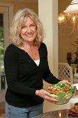 A beautiful, mature woman with serving a healthy green salad.