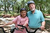 An attractive senior couple bicycling together wearing helmets.