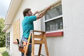 A man measuring windows for hurricane shutters or plywood.