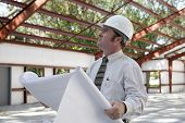 A construction inspector holding blueprints and looking at the roof beams of a steel building in pro