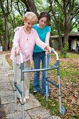 Teen girl helps her aging grandmother to walk using a walker.