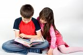 image of girl reading book  - sister with brother reading a book at home - JPG