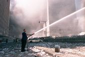 NEW YORK - SEPTEMBER 11:  An unidentified civilian uses a fire hose as he works near the area known