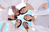 Groep van gelukkige jonge mensen in cirkel op strand veel plezier en glimlach