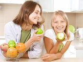 Happy Mother with Daughter eating Healthy food. Diet. Healthy Eating Concept