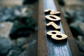 closeup of four wooden numbers forming the number 2018, as the new year, on a rail of a railway, met poster