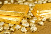 stock photo of gold nugget  - fine gold ingots and nuggets on a wet golden background
