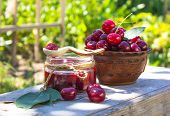 Cherry Jam. Glass Jar Of Cherry Jam And Fresh Berries On Wooden Table With Green Blurred Natural Bac poster