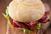Sandwich with salami on chopping board