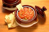 Salsa bowl with corn chips on a rustic wooden table