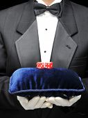 Butler in tuxedo holding blue velvet pillow and red dice