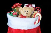 Christmas Stocking Filled With Toys, Candy Cane and Presents over black background