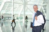 Middle Aged Business Traveler in Airport Concourse with blurred travelers in background