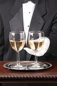Close up of a Waiter With Two Glasses of Chardonnay on a silver tray and fancy wood table vertical f
