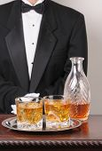 Waiter in tuxedo with Cocktails and Decanter on tray and wood table vertical format torso only