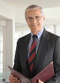 Portrait of a middle aged businessman in modern office building holding a leather portfolio. Vertica