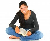 Smiling female teenage student sitting with her legs crossed with open book in her lap. Horizontal f